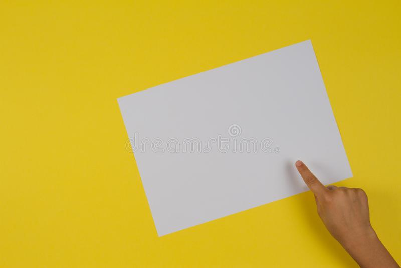 Dedo da mão das crianças que aponta ao cartão de papel vazio branco no fundo amarelo imagens de stock royalty free