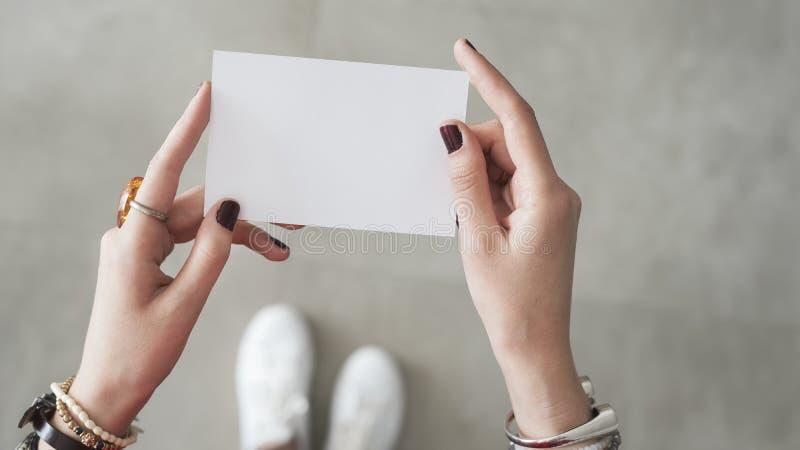 Dedo da mulher ambo mão que guarda o cartão branco imagens de stock royalty free