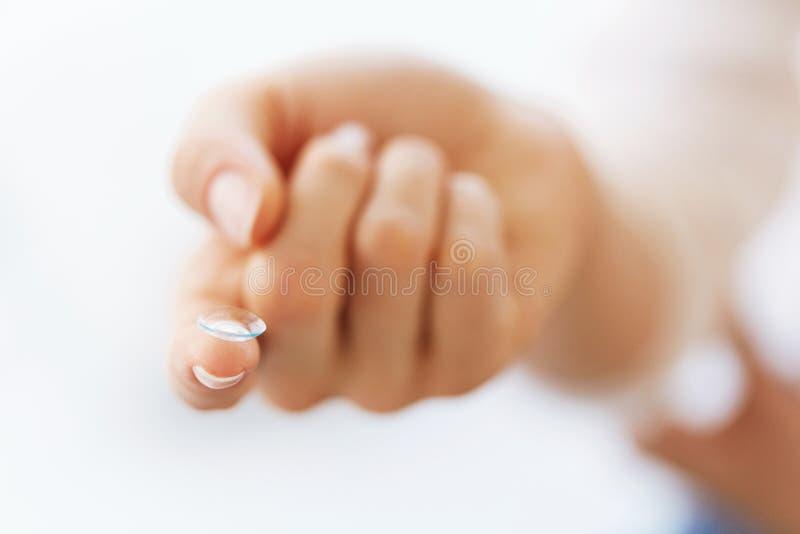 Dedo da mulher com a lente de olho do contato Eyecare da visão fotografia de stock