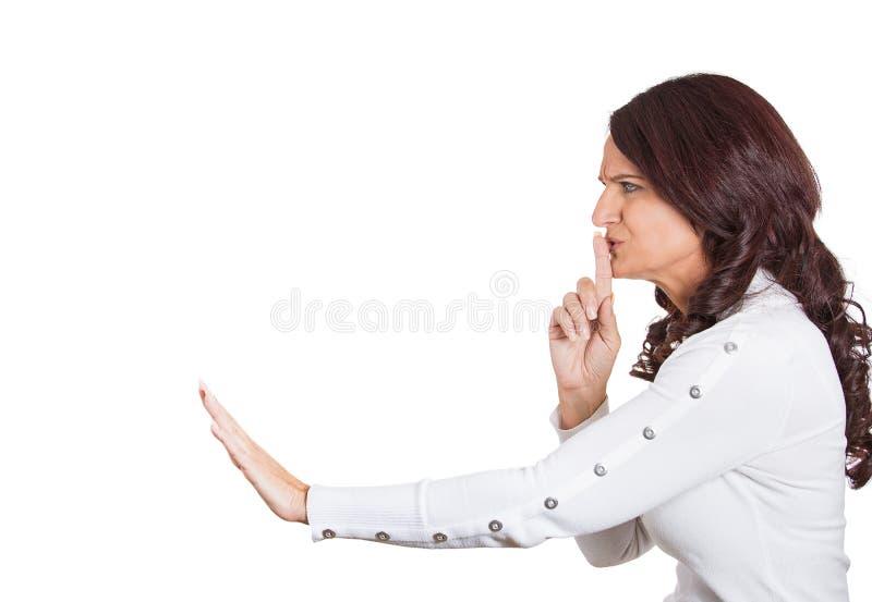 Dedo da mulher nos bordos que apontam em alguém o segredo quieto foto de stock