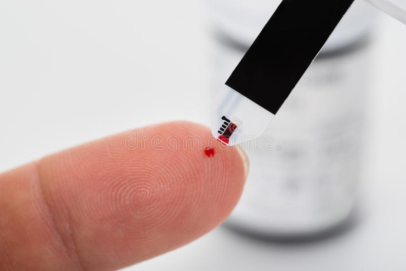 Dedo da pessoa com um glucometer foto de stock