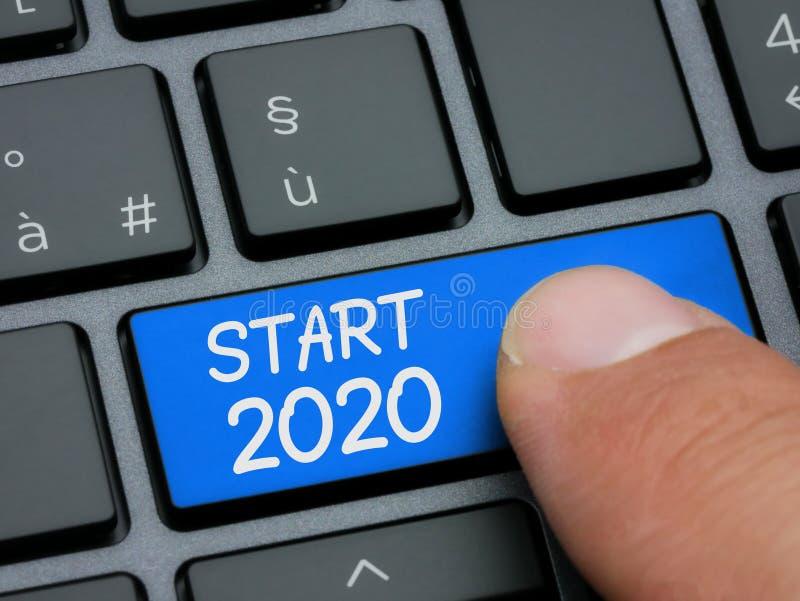 Dedo do close up que datilografa na chave do começo 2020 no teclado de computador foto de stock