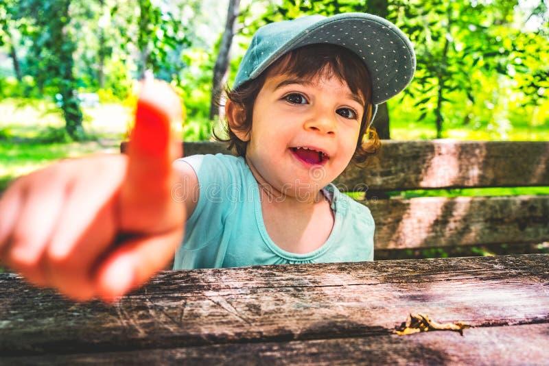 Dedo do ponto da criança do menino impertinente na natureza b do retrato da provocação da câmera foto de stock