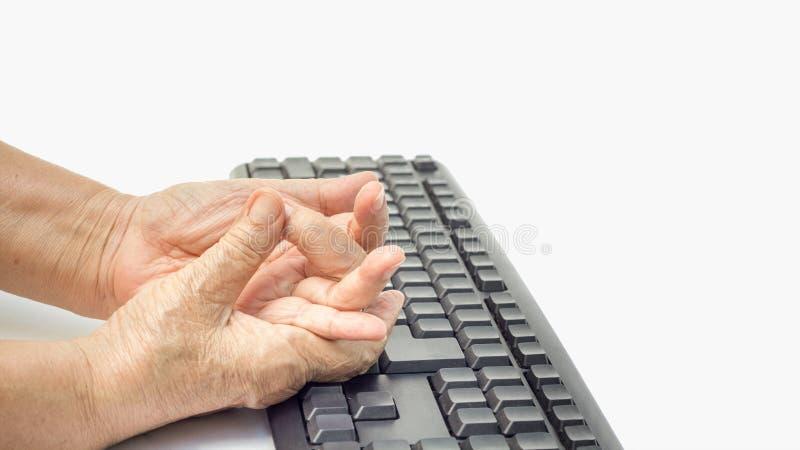 Dedo doloroso da mulher superior devido ao uso prolongado do teclado fotos de stock royalty free