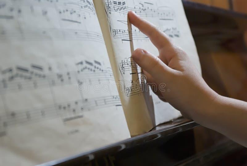 Dedo en la hoja de música imagen de archivo