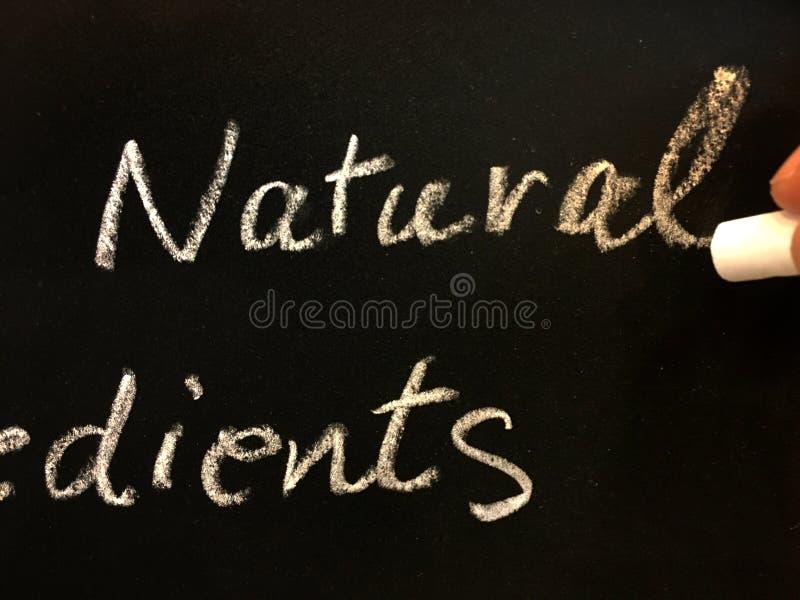 Dedo feminino segura giz branco e escreve palavra natural no quadro-negro para explicar a descrição do produto foto de stock royalty free