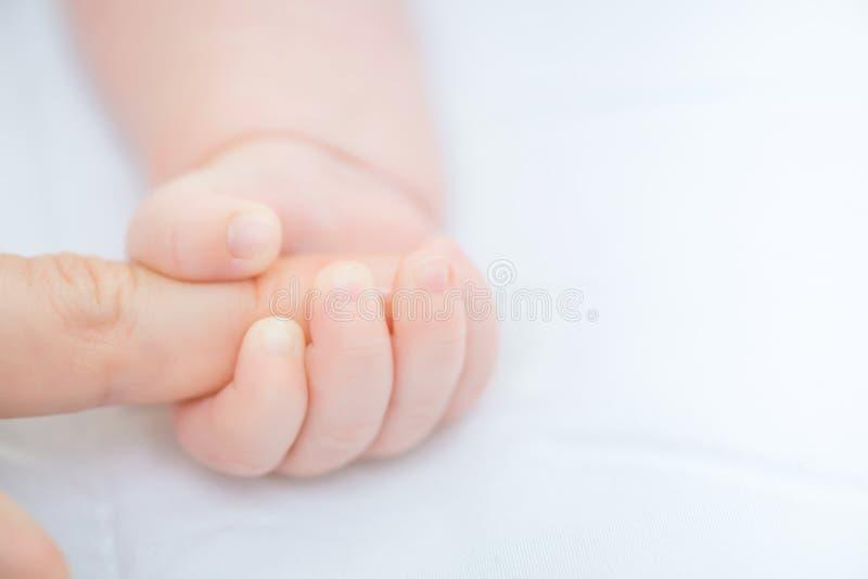 Dedo guardando infantil da mãe fotografia de stock