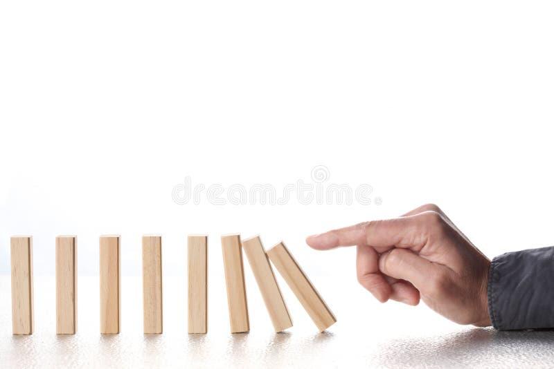 Dedo masculino que empurra blocos do dominó com o isolado de queda da reação em cadeia no fundo branco com espaço da cópia p foto de stock royalty free