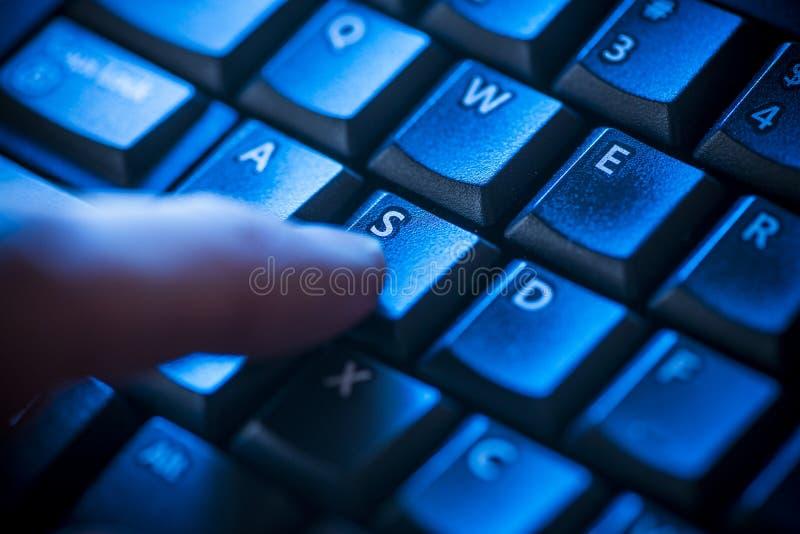 Dedo no teclado na luz azul imagens de stock
