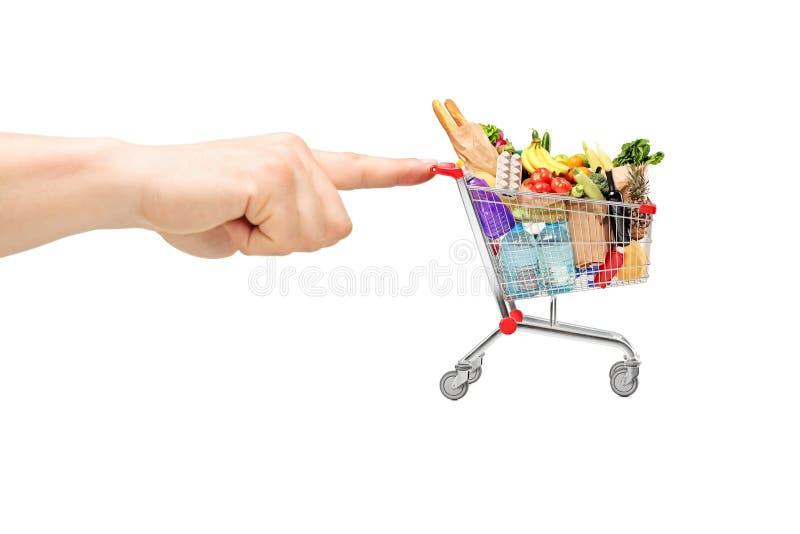Dedo que empurra um carrinho de compras completamente dos produtos alimentares imagem de stock
