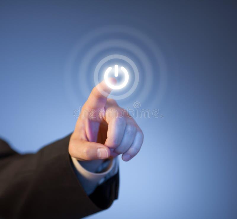 Dedo que presiona el botón virtual de la potencia en la pantalla fotografía de archivo libre de regalías