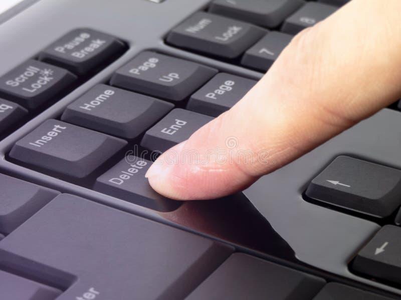Dedo que pressiona o botão da supressão no teclado preto imagens de stock