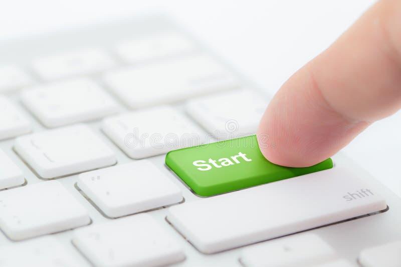 Dedo que pressiona a tecla 'Iniciar Cópias' verde no teclado imagem de stock