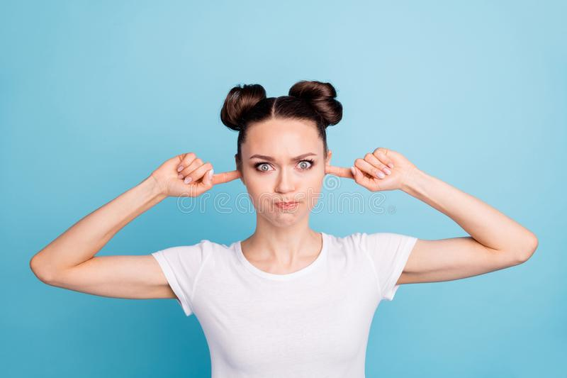 Dedos índices bonitos de la señora dentro de los oídos que llevan a cabo el fondo azul de la camiseta casual blanca cambiante del imagen de archivo libre de regalías