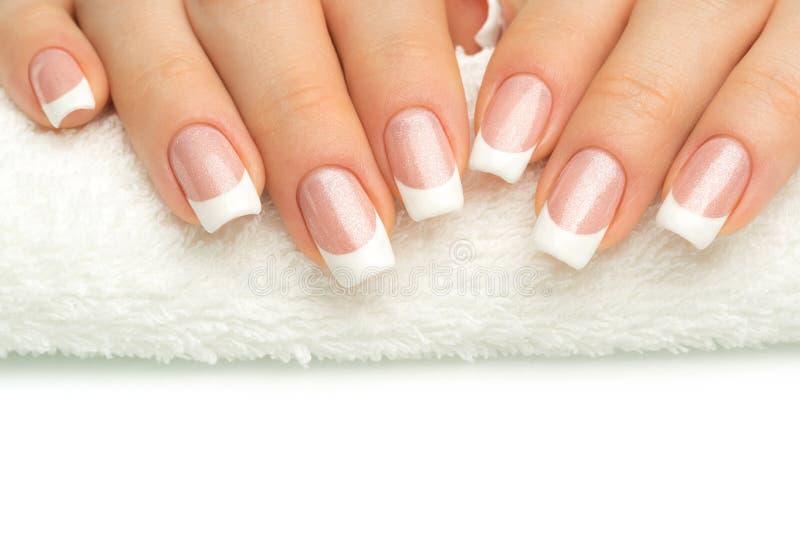 Dedos bonitos com tratamento de mãos francês na toalha Tratamento de mãos dentro imagem de stock royalty free
