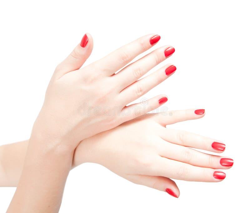 Dedos com os pregos vermelhos no branco. fotografia de stock royalty free