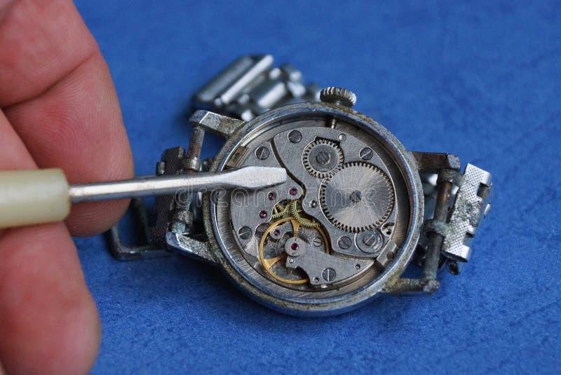 Dedos com uma chave de fenda no pulso de disparo cinzento velho com um mecanismo aberto imagens de stock royalty free