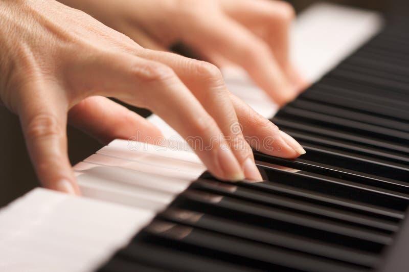 Dedos da mulher em chaves do piano de Digitas foto de stock