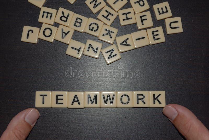 Dedos das letras da telha que soletram trabalhos de equipe em um fundo preto com letras misturadas na parte superior Conceito par fotos de stock
