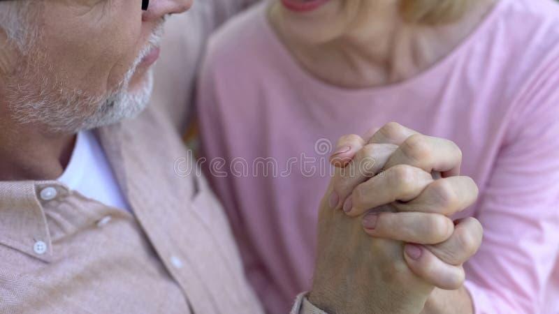 Dedos de cruzamento aposentados românticos dos pares, guardando as mãos, avós felizes foto de stock royalty free