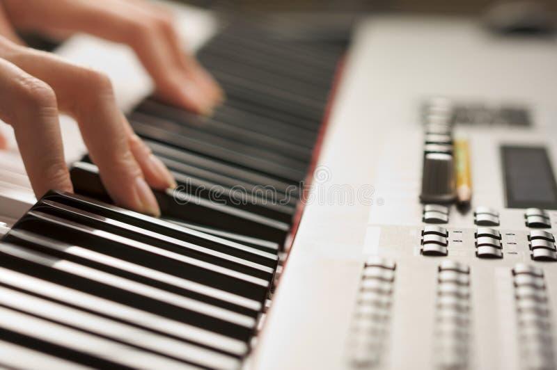 Dedos de la mujer en claves del piano de Digitaces fotos de archivo libres de regalías