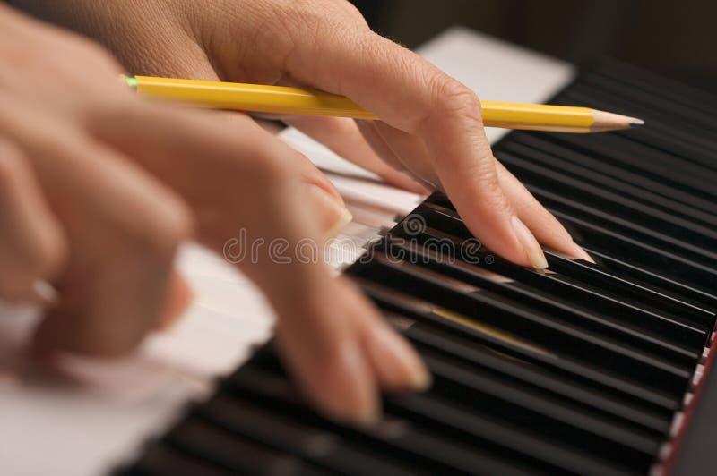Dedos de la mujer en claves del piano de Digitaces imagen de archivo libre de regalías