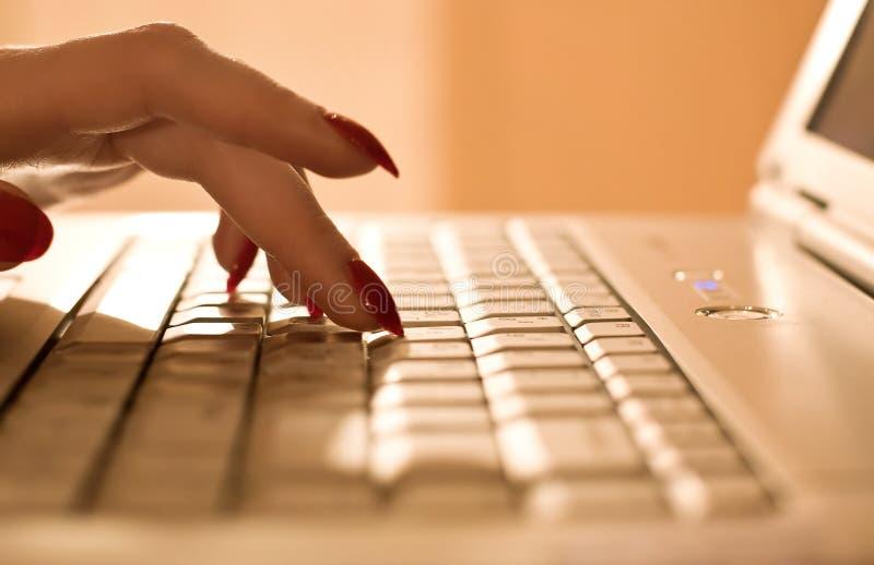 Dedos de la mujer en el teclado de la computadora portátil imagenes de archivo