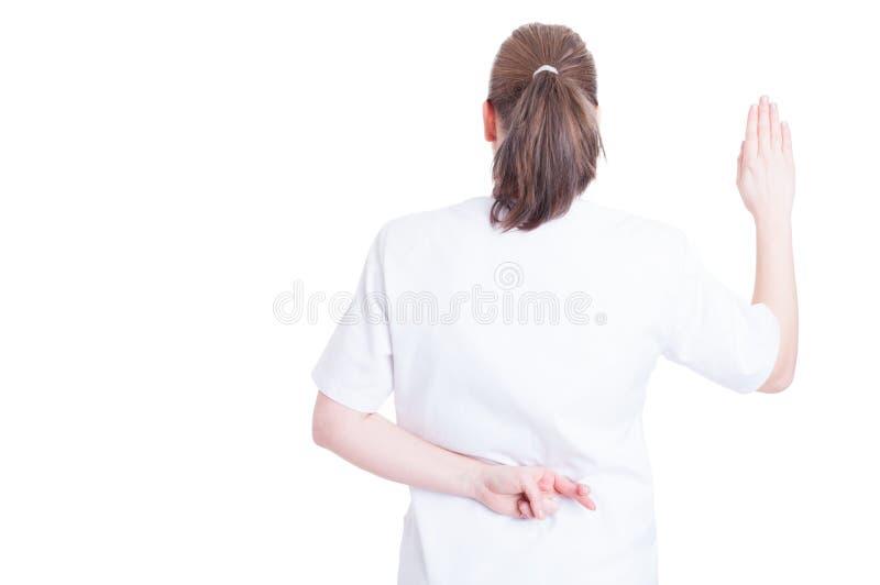 Dedos do cruzamento do doutor da mulher atrás dela para trás fotografia de stock
