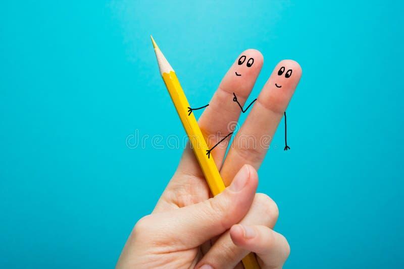 Dedos engraçados que tiram mantendo o lápis amarelo contra o fundo azul Imagem conceptual da motivação foto de stock royalty free