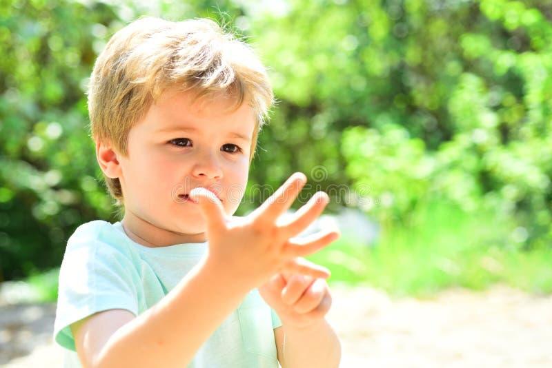 Dedos espertos das contagens da criança O menino terá cinco anos velho Uma criança bonita mostra sua mão, uma palma pequena Crian fotos de stock