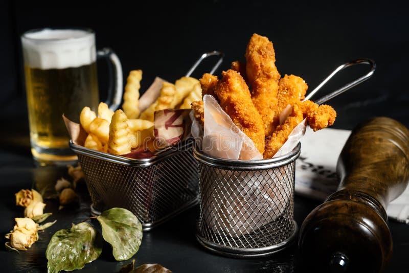 dedos frescos saborosos, de dar água na boca da galinha com fritadas e cerveja imagens de stock royalty free