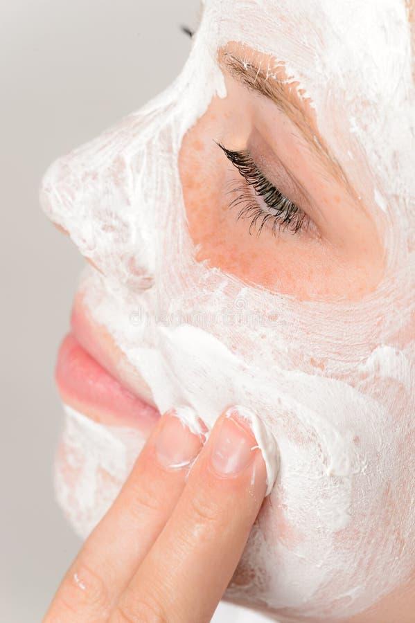 Dedos que aplicam a rapariga do creme hidratante da máscara protetora foto de stock