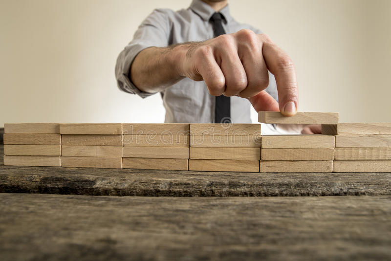 Dedos que colocam o bloco de madeira na pilha em ordem imagem de stock royalty free