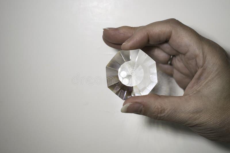 Dedos que guardam um prisma claro foto de stock
