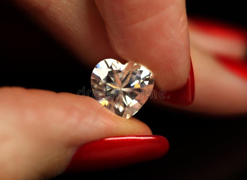 Dedos que sostienen el diamante de la dimensión de una variable del corazón fotografía de archivo