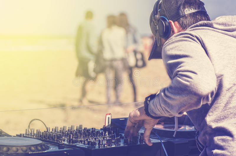 Dee Jay mixing at beach party. Dj playing music at a beach party royalty free stock photo