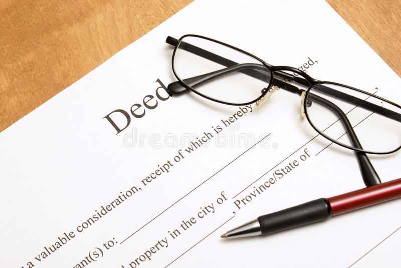 Deed Papers. A closeup shot of deed papers and glasses to read the fine print royalty free stock images