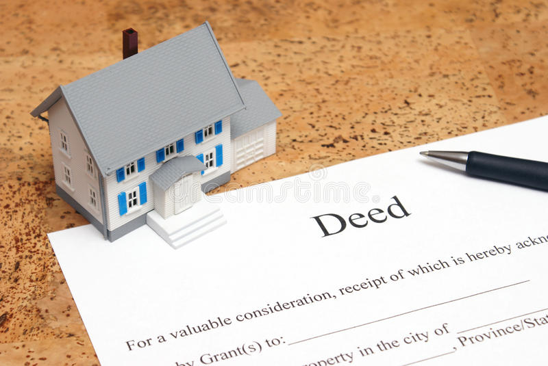 Deed to a House. A scale house on some forms for a deed to conceptualize on the financial investment stock photography