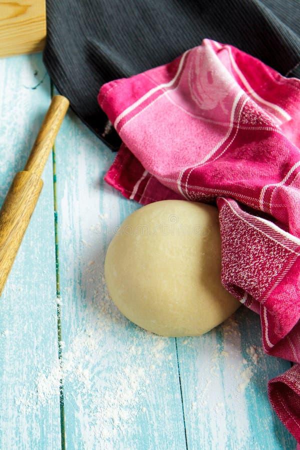 Deeg, deegrol en roze handdoek op lichtblauwe raad stock foto's