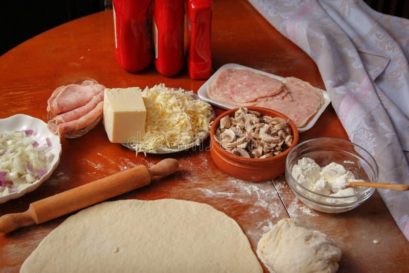 Deeg voor pizza en verse ingrediënten klaar voor voorbereiding op houten lijst royalty-vrije stock fotografie