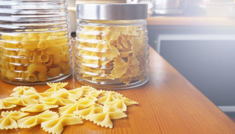 Deegwaren in de vorm van bogen die van glaskruik worden verspreid Italiaanse met de hand gemaakte deegwaren stock foto