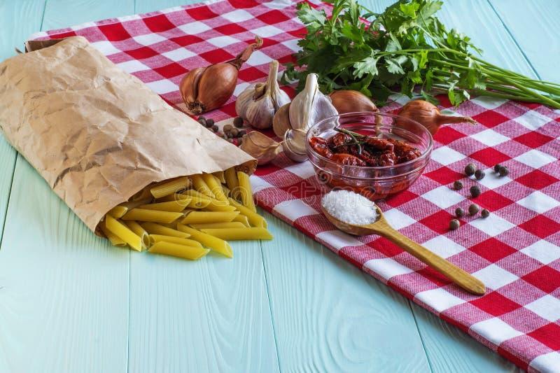 Deegwaren, in de zon gedroogde tomaten, uien, knoflook, kruiden in houten royalty-vrije stock afbeeldingen