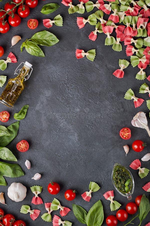 Deegwaren farfalle, kersentomaten, knoflook, olijfolie en basilicum op donkere achtergrond met exemplaarruimte royalty-vrije stock afbeeldingen