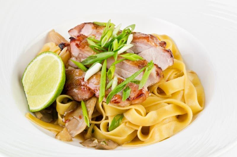 Deegwaren Fettuccine en gekarameliseerd varkensvlees met groene uien en kalk royalty-vrije stock foto