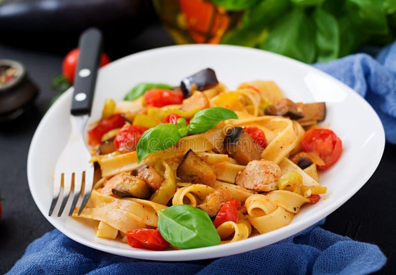 Deegwaren Fettuccine met tomaat, aubergine en kip stock foto