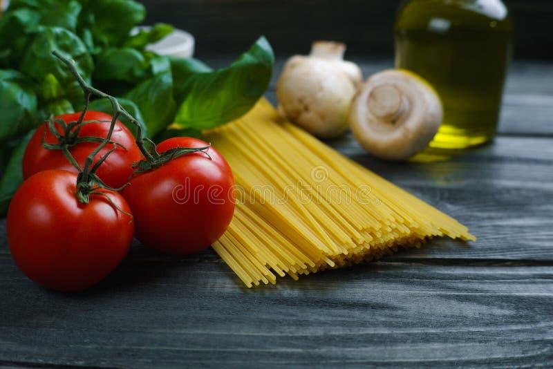 Deegwaren kokende ingrediënten Ruwe spaghetti, tomaten, basilicum, olijf stock fotografie
