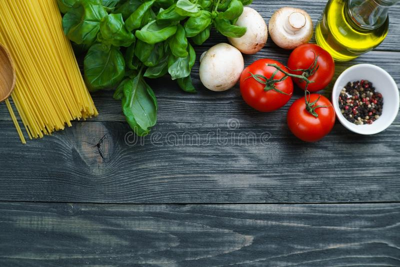 Deegwaren kokende ingrediënten Ruwe spaghetti, tomaten, basilicum, olijf stock foto's