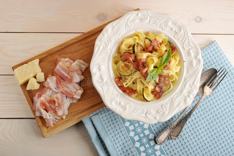 Deegwaren met bacon, courgette en kaas in een kom royalty-vrije stock afbeelding