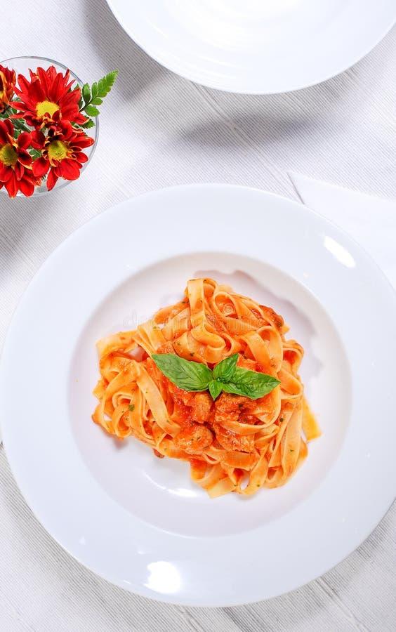 Deegwaren met basilicum en tomatensaus op wit wordt geïsoleerd dat stock foto