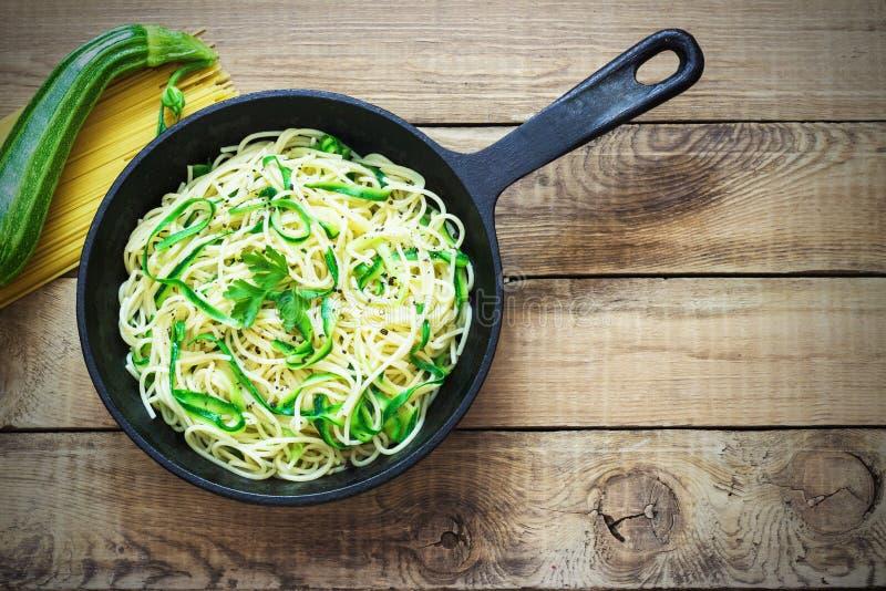 Deegwaren met courgette op donkere houten achtergrond in een gietijzerpan Spaghetti van organische wholegrain bloem royalty-vrije stock foto